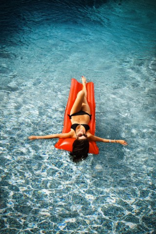 Young woman on inflatable mattress in swimming pool